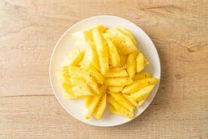 Fresh pineapple sliced on white plate photo