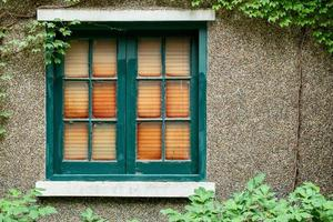 Antique wooden window frame on stone wall photo