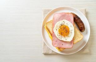 Pan casero con queso tostado, jamón y huevo frito con salchicha de cerdo y café para el desayuno. foto