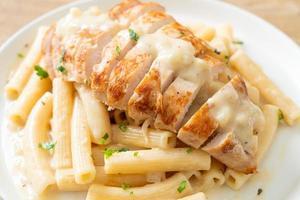 Pasta casera quadrotto penne salsa cremosa blanca con pollo a la parrilla foto