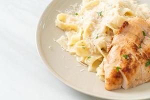 Pasta fettucine casera salsa cremosa blanca con pollo a la parrilla foto
