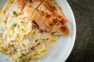 Espaguetis caseros en salsa cremosa blanca con pollo a la parrilla foto