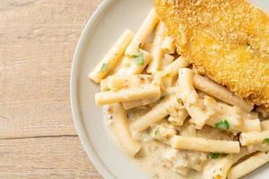 Homemade quadrotto penne pasta white cream sauce with fried fish photo