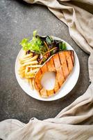 Grilled salmon steak fillet with vegetable and french fries on plate photo