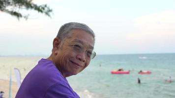 retrato de hombre mayor con rostro sonriente. fondo de playa y mar video