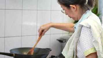 close-up de mulher asiática sênior cozinhando comida na cozinha video