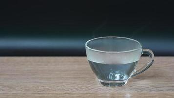 slow motion of steam from  hot water in glass served on table video