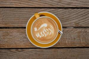 Top-view of a cup of cappuccino with latte art at the wooden table photo