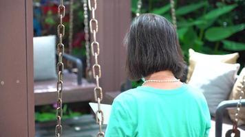 retrato de mulher asiática aposentada lendo e-book no jardim video