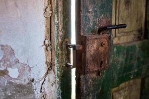 Closeup shot of an old weathered padlock on a door photo