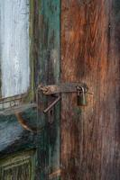 Vertical shot of a rusted lock on an old wooden door photo