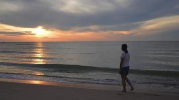 jonge aziatische vrouw die bij zonsopgang op het strand loopt video