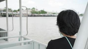 middle age woman wearing face mask sitting in boat to cross river video