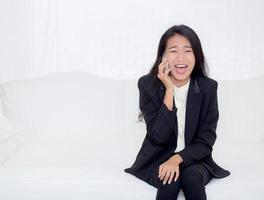 Asian woman talking phone in the living room photo