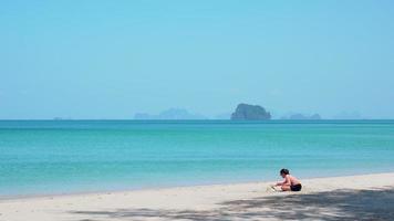ung asiatisk tjej som leker sand på stranden under sommarlovet video