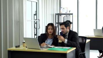 caucasian manager train asian trainee to work in office video