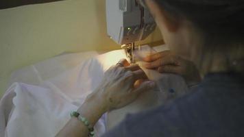Mujer mayor con máquina de coser para coser ropa en casa video