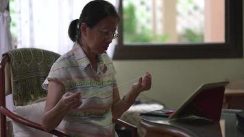 mulher idosa bordando em casa video