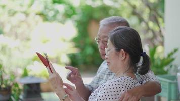 senior asian couple using digital tablet together in garden video