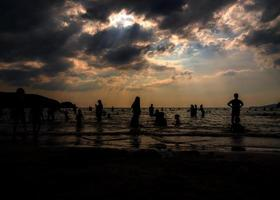 Silhouettes of people playing in the sea at a public beach photo
