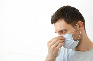 Coronavirus. Quarantine. A man puts on a mask. Virus protection. photo