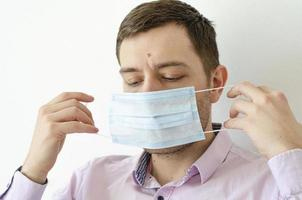A man in a shirt puts on a mask. Virus protection. photo