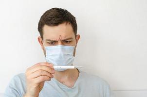 un hombre mide la temperatura. calor. en la máscara. foto