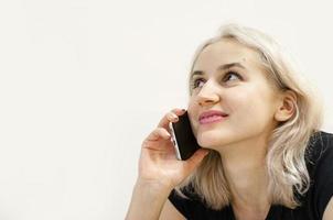 una joven de cabello rubio se comunica por teléfono. foto