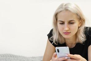 la niña lee malas noticias por teléfono. redes sociales. foto