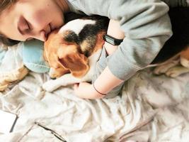 niña y perro beagle duermen juntos. niña abraza a un perro. mascota en casa. amor. foto