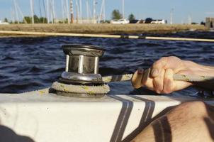 guapo trabajando en velero. deporte acuático. foto