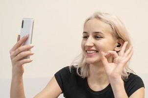 Girl communicates by video call. Wireless headphones. photo