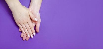 manicura femenina sobre un fondo brillante. púrpura foto