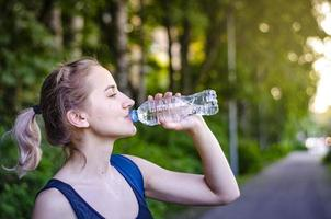 Beautiful girl drinking water after exercise. Playing sport. photo
