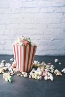 popcorn spilling from a container on a table photo