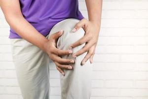 Cerrar sobre el hombre que sufre dolor en las articulaciones de la rodilla foto