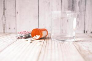 medical pill, blister pack and glass of water on table photo