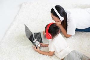 asian mother teaching child to study from computer program at home photo