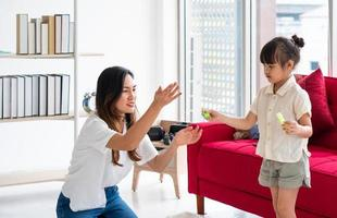 asian mother playing blowing bubbles with child in living room photo