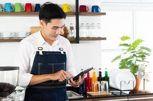 young asian barista taking order of coffee in cafe photo
