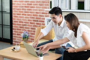 young asian man using computer to work with his colleague in the cafe photo