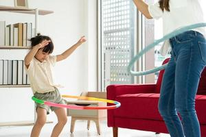 asian kid playing hula hoop with mother in living room in summer time photo