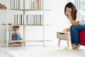 Niño asiático jugando al escondite con los padres en casa foto