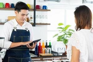 young barista taking order of coffee from customer in cafe photo