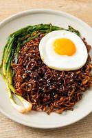Homemade dried Korean spicy black sauce instant noodles with fried egg and kimchi photo