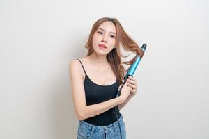 Portrait beautiful Asian woman using hair curler or curling iron on white background photo