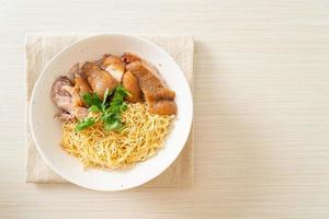 Tazón de fideos de pierna de cerdo guisados secos - estilo de comida asiática foto