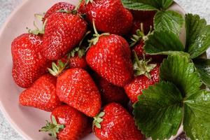 Beautiful juicy fresh strawberries on the concrete surface photo