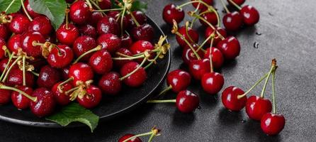 Fresh delicious red bright cherry berries torn in the summer garden photo