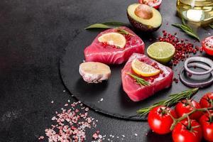 Filetes de atún fresco con especias y hierbas sobre un fondo negro foto